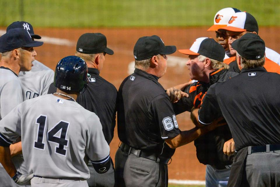 The Orioles' Buck Showalter is restrained from going after Yankees counterpart Joe Girardi (left) in the first inning.