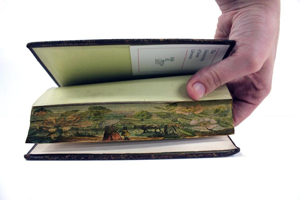 An unidentified artist adorned a book using a technique known as fore-edge painting, in which the book is fanned open using a special press, which allows the artist to create paintings that unfold across the margins of the pages.