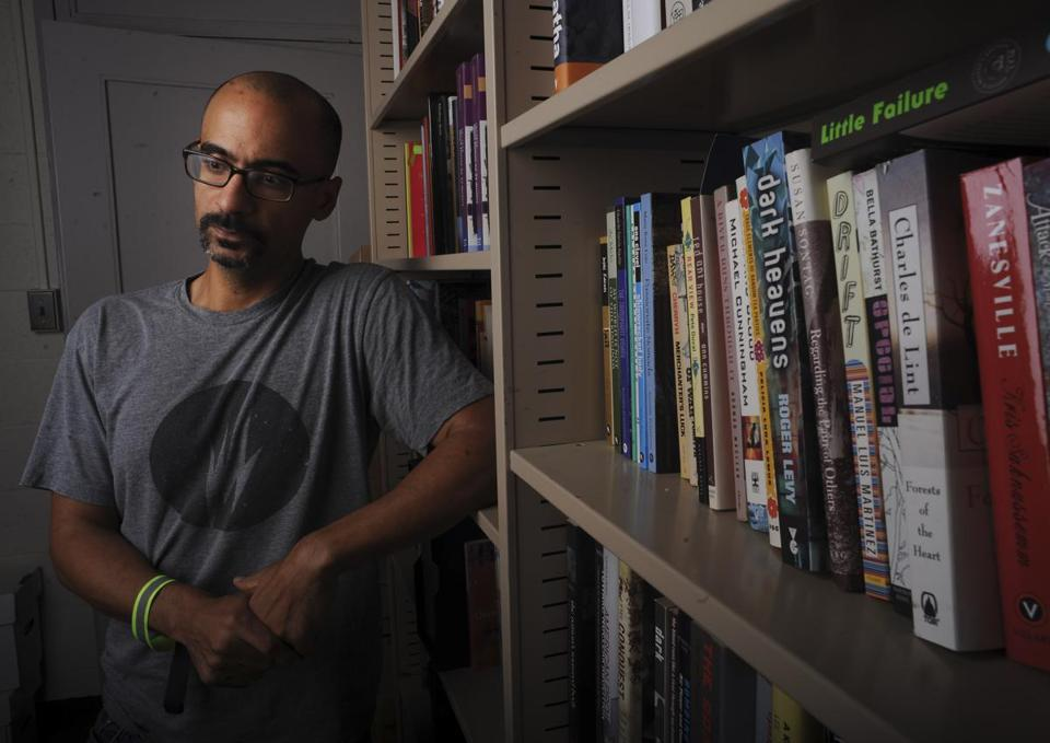 Author Junot Diaz at his office at MIT which is populated by lots of books and an action hero figure.