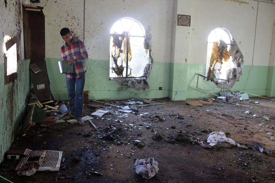 A man looked through debris in a Sunni mosque near the Iraqi city of Baqouba after a bomb killed 33 worshipers.