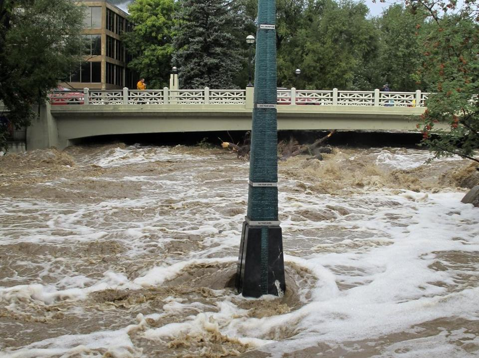 Rain-swollen Boulder Creek flowed around a marker that shows historic flood levels on Friday in Boulder, Colo.