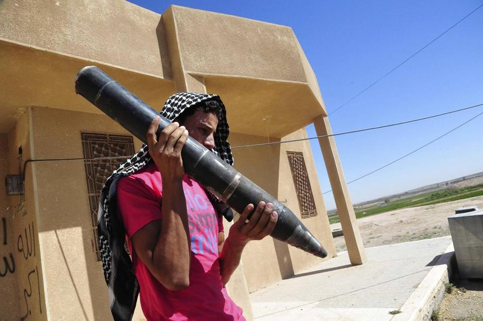 A Free Syrian Army fighter carried a shell in the suburb of Raqqa, in eastern Syria.