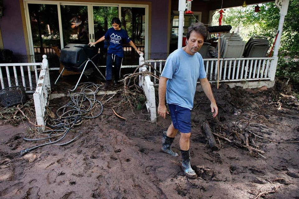 Allen Tawa and his daughter Kayla walked out of their mud-clogged home after days of flooding, on the edge of Boulder, Colo., on Saturday. Not all were willing to leave the area.