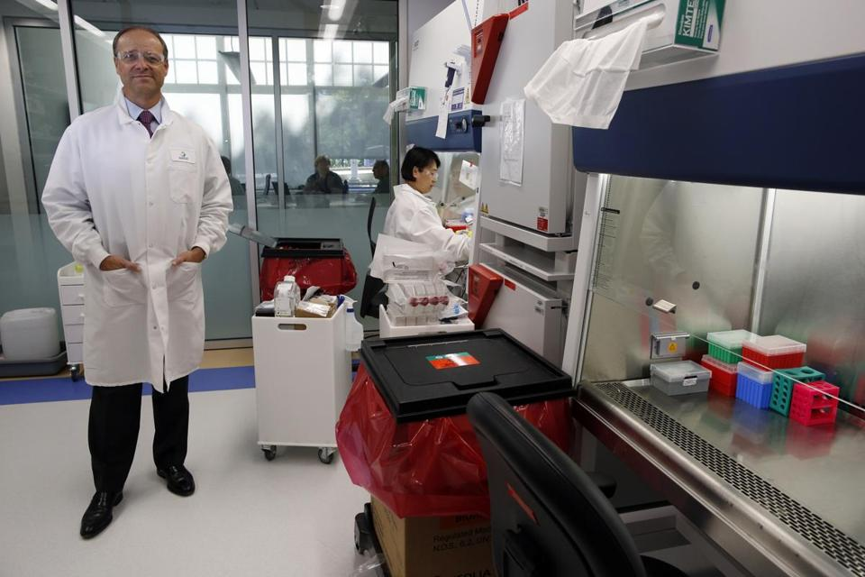 Sanofi chief executive Chris Viehbacher (left ) visited the firm's lab in Cambridge, where research associate Lan Jiang was working on Wednesday.