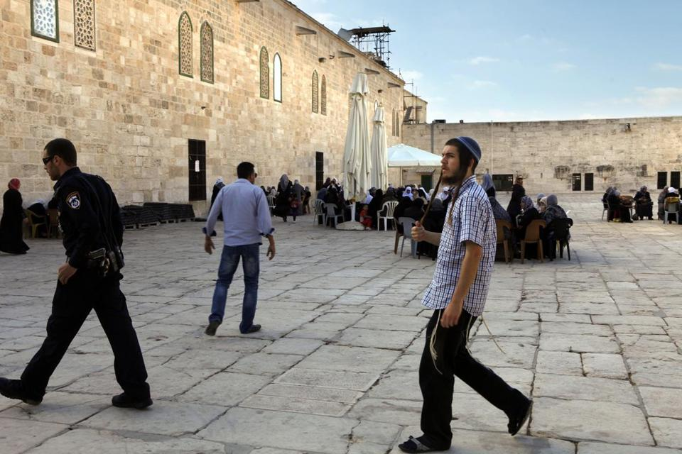 A security officer escorted a Jewish man at Al Aksa Mosque on the Temple Mount in the Old City of Jerusalem. There are rules against non-Muslim prayer there.
