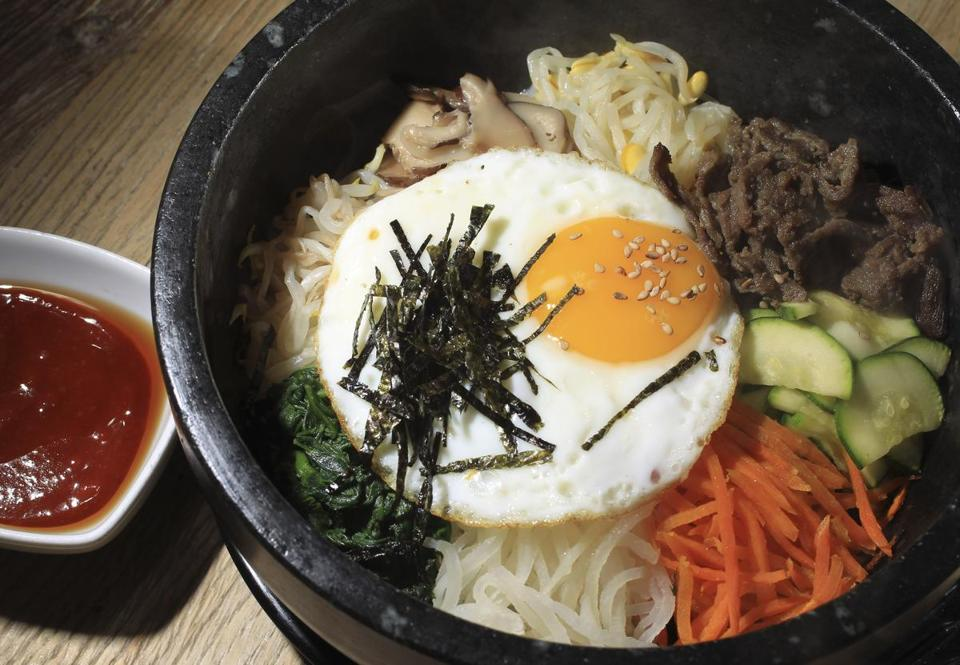 Among dishes served is jjolmyun, cold noodles with chili sauce, cucumbers, red cabbage, and a yolked egg.