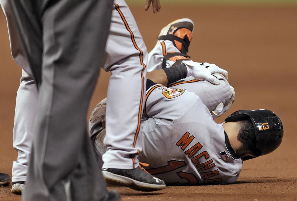 Orioles All-Star Manny Machado grabs his left leg after it buckled running to first. He was taken off on a stretcher.
