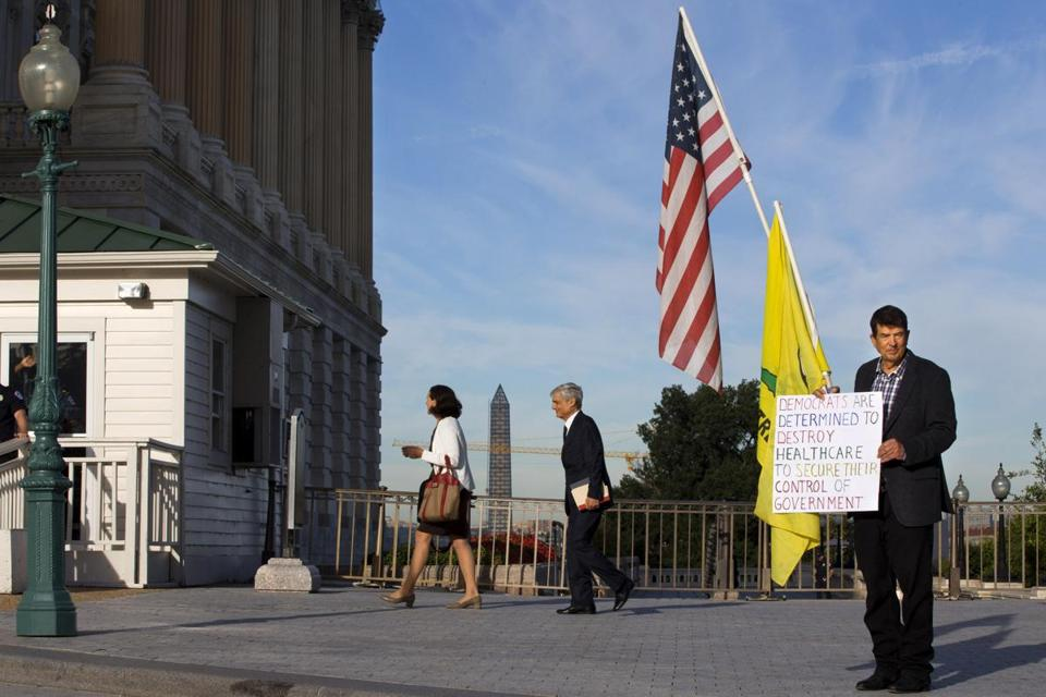 A member of the Tea Party  held a sign against the health care law outside the Senate side of the Capitol in Washington, D.C., on Wednesday.