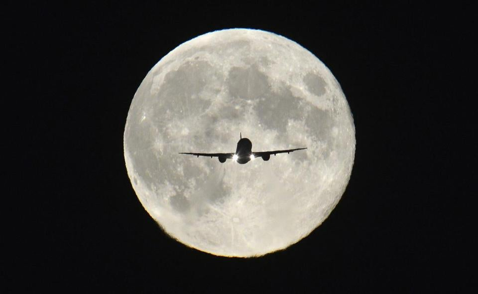 A plane in front of the harvest moon.
