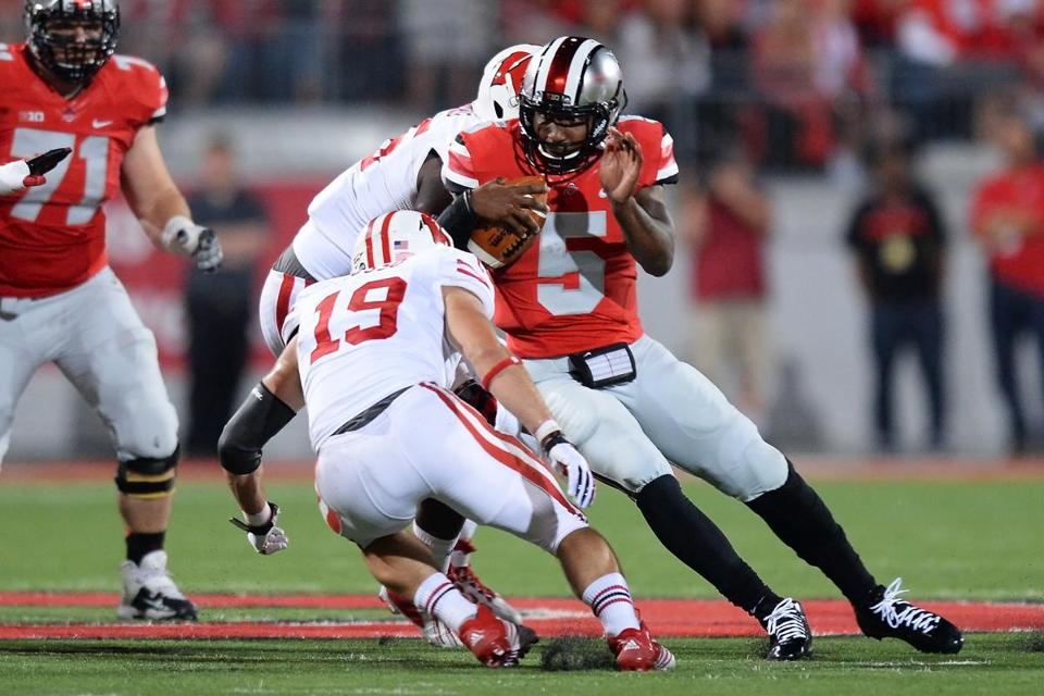 Ohio State's Braxton Miller, who missed two games with a knee injury, gets caught between two Wisconsin defenders.