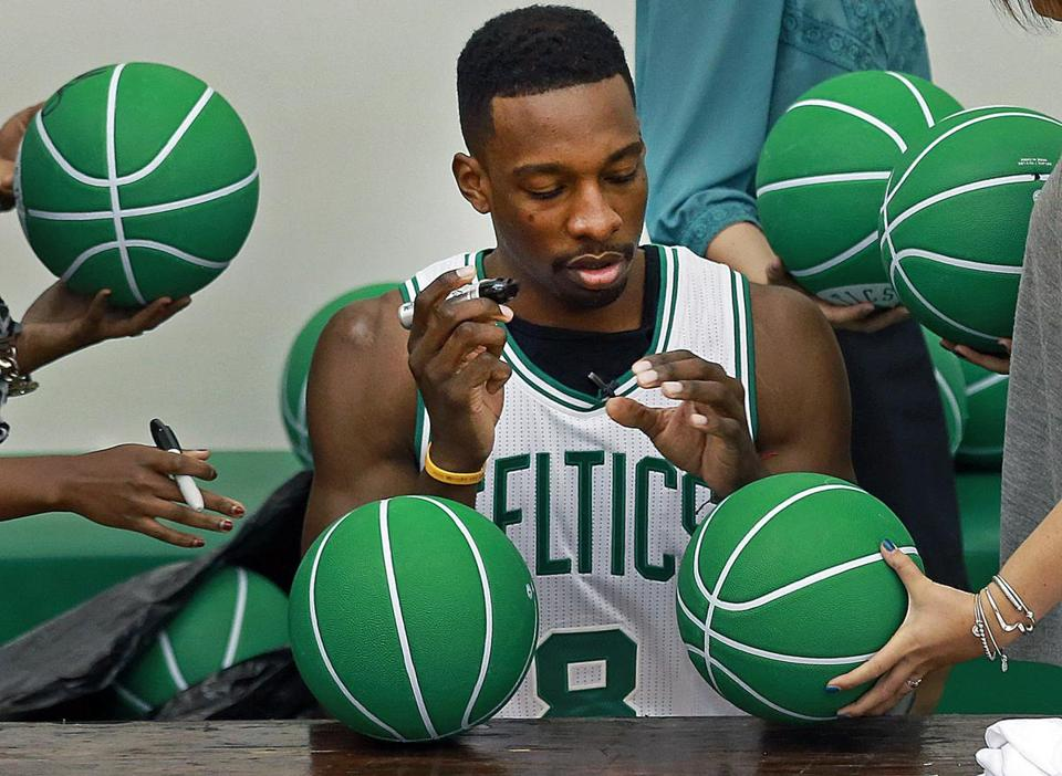 Jeff Green signs — of course — green basketballs, assembly-line style, on media day.