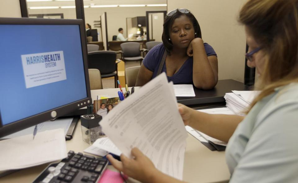 Harris Health counselor Lillian Ardon (right) helped Vanessa Cotton with her insurance application Tuesday in Houston.