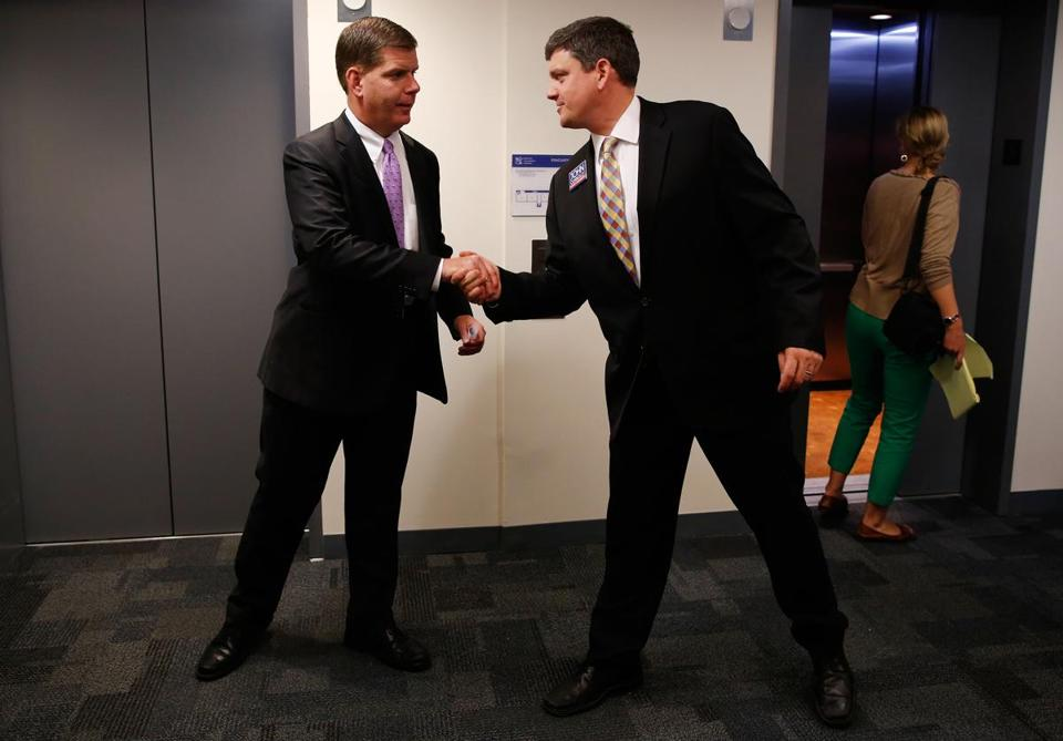 Mayoral candidates Marty Walsh (left) and John Connolly shook hands Wednesday as they crossed paths at a school presentation in Roxbury. Later in the day, Connolly abnd Walsh took turns being questioned by members of the Massachusetts Association of Minority Law Enforcement Officers.