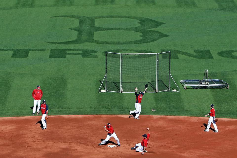 With the Boston Strong logo that grew out of the Marathon bombings cut into the outfield, the Sox work out Tuesday.