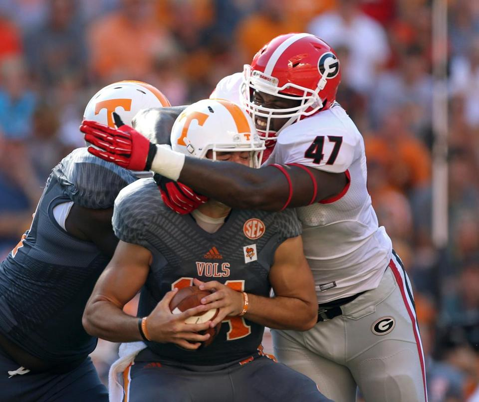 Tennessee quarterback Justin Worley can't escape the grasp of Georgia's Ray Drew, who gets the first-half sack.