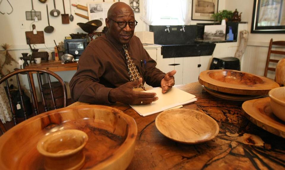 Willie Wilson at a table made from a slice of Brockton's Liberty Tree.