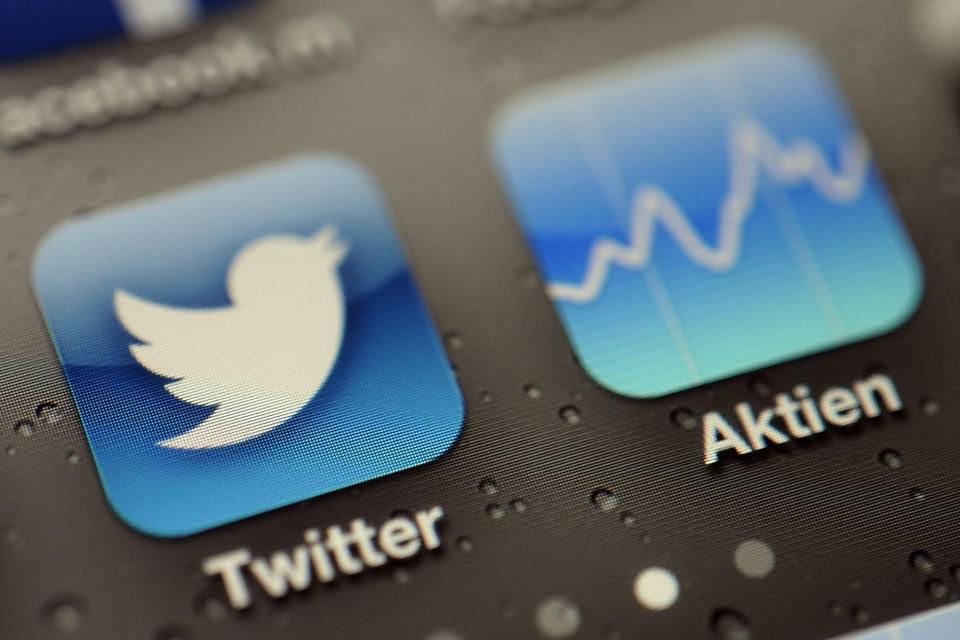 FILE - This Sept. 13, 2013, file photo shows a Twitter App and stock tracker on an iPhone, in Koln, Germany. Twitter's stock debut is the biggest coming-out party since Facebook, and Wall Street's marquee exchanges are fighting to host it. (AP Photo/dpa, Marius Becker, File)