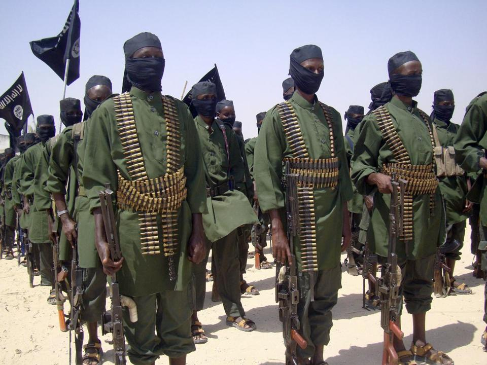 Al Shabab fighters stood in formation with their weapons during military exercises near Mogadishu, Somalia.