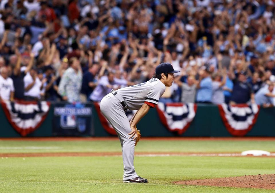 Koji Uehara is  hunched over after the Rays' Jose Lobaton hit a walkoff solo home run off him in the ninth inning.