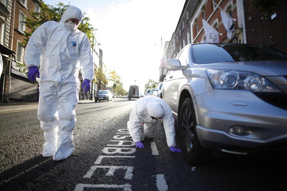 Forensic officers examined a car near where a man was shot dead in Londonderry, Northern Ireland, on Thursday,