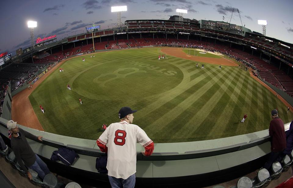 "In this image made with a fisheye lens, Sam Champey watches batting practice from the ""Green Monster"" before Game 2 of the American League baseball championship between the Boston Red Sox and the Detroit Tigers series Sunday, Oct. 13, 2013, in Boston. (AP Photo/Charlie Riedel)"