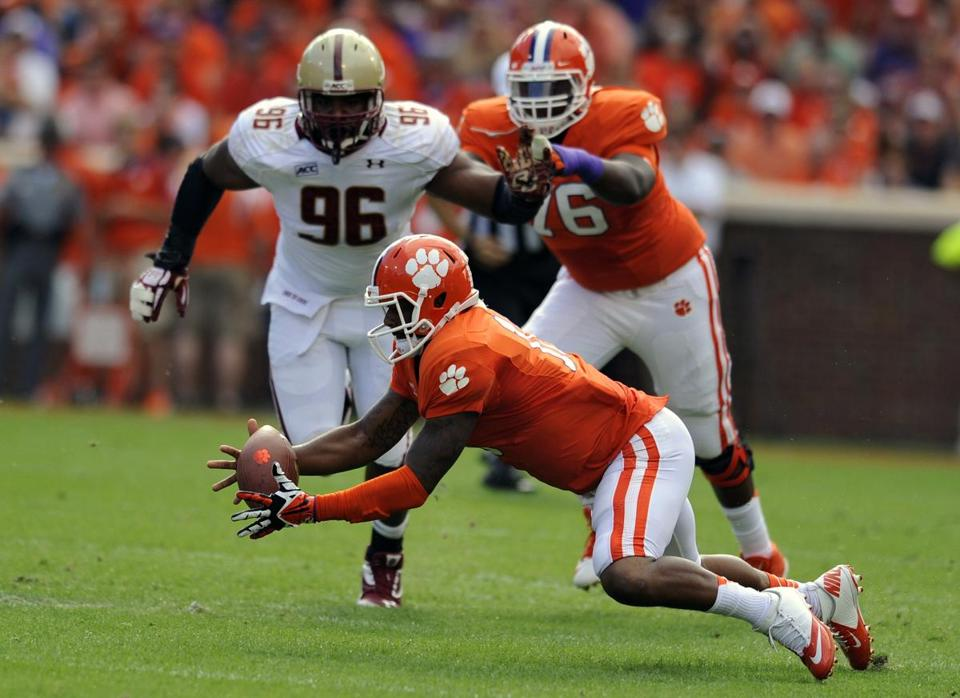 Clemson quarterback Tahj Boyd (center) recovered his own fumble while Boston College's Kaleb Ramsey pursued him.