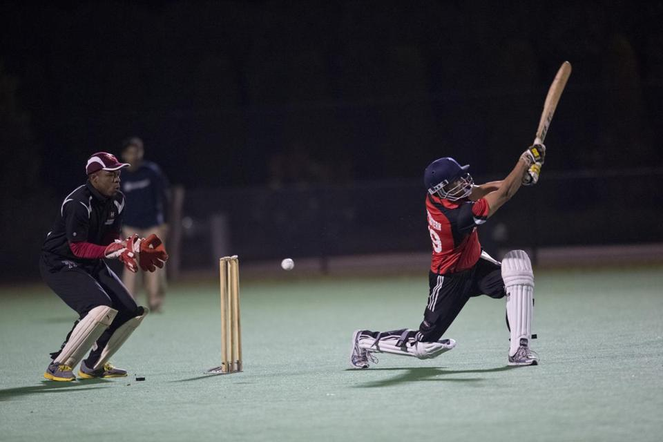 Northeastern's Mihir Shah swings and misses in front of Harvard's Norris Guscott at Jordan Field.