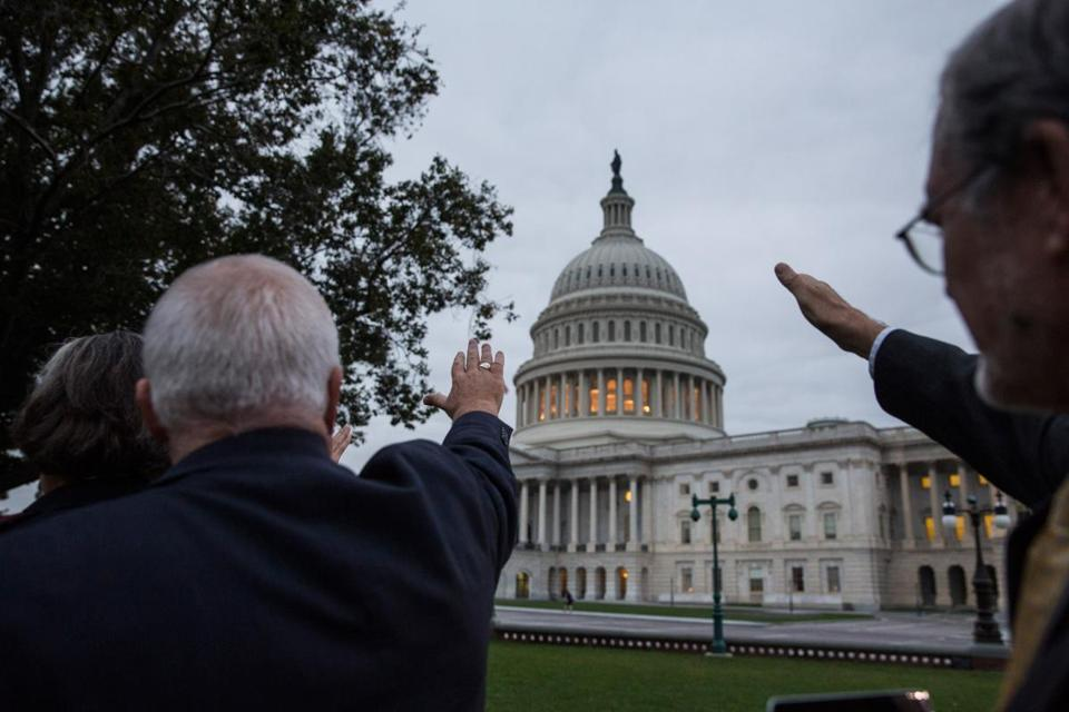 Religious leaders raised their hands in prayer towards the Capitol building on Wednesday morning.