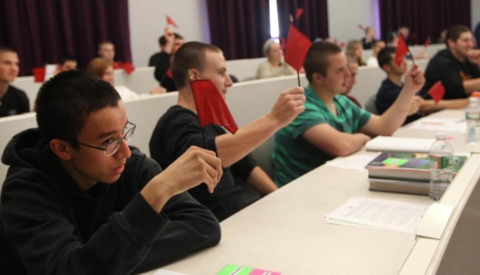 Shawsheen Valley Tech students wave red flags to signal a warning of fraud during an exercise in CSBsmart, a financial literacy course.