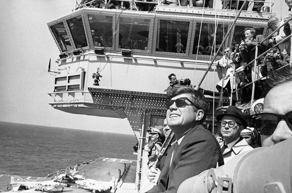 President John. F. Kennedy looks into the sky as planes from the Carrier Enterprise maneuver in a demonstration off the east coast on April 14, 1962.