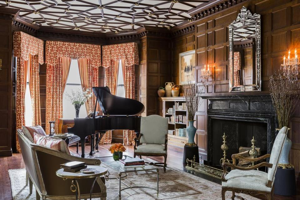 A Moroccan fretwork ceiling, original quartersawn-oak paneling, and black marble fireplace are just a few of the living room's dramatic features.