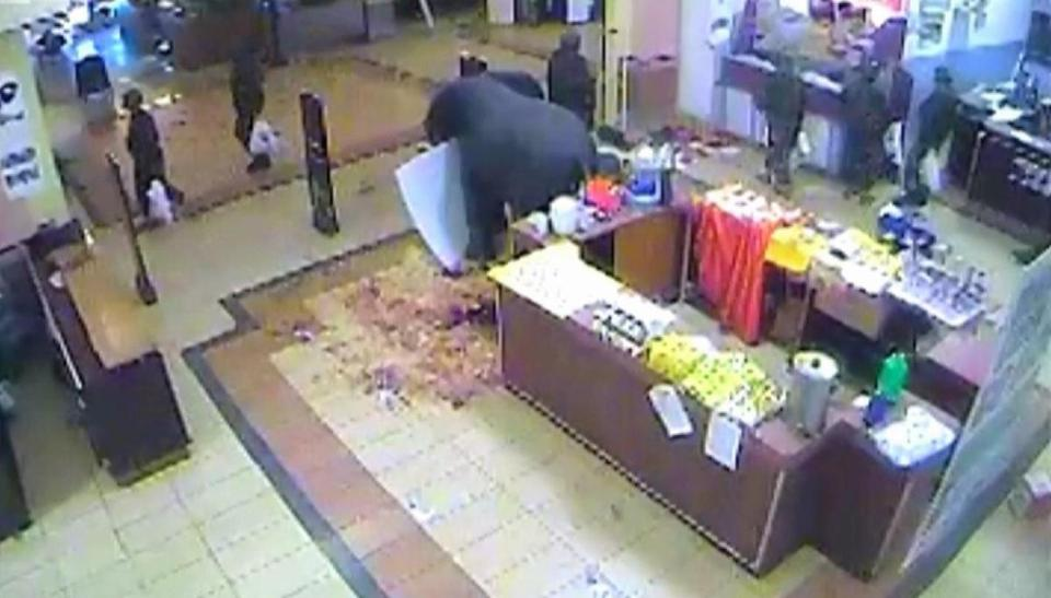 In a security video, Kenyan soldiers (top) exit a Westgate Mall store with full shopping bags.