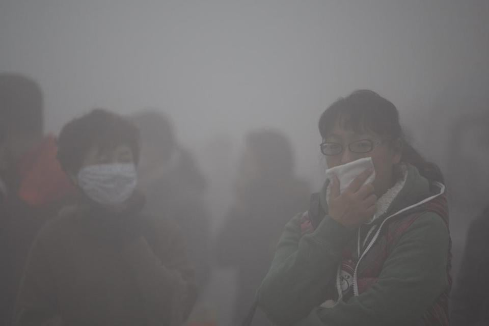 Commuters covered their mouths while waiting for buses in the heavy fog and smog in Harbin, China. Visibility was so low in places that vehicles lost their way.
