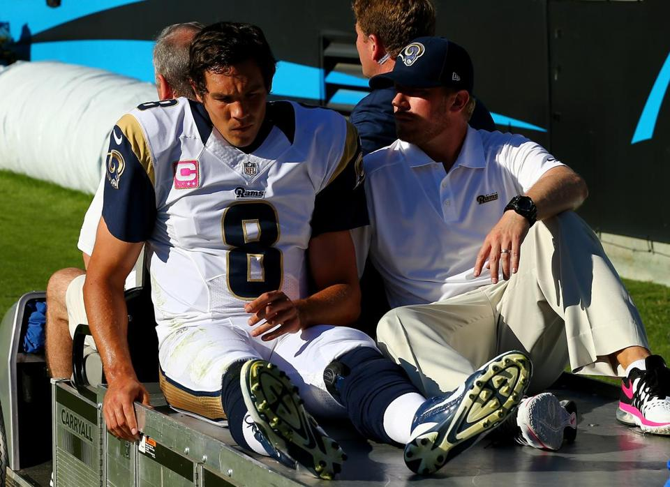 The Rams' Sam Bradford is carted off after being knocked out of bounds — and lost for the season — on Sunday.