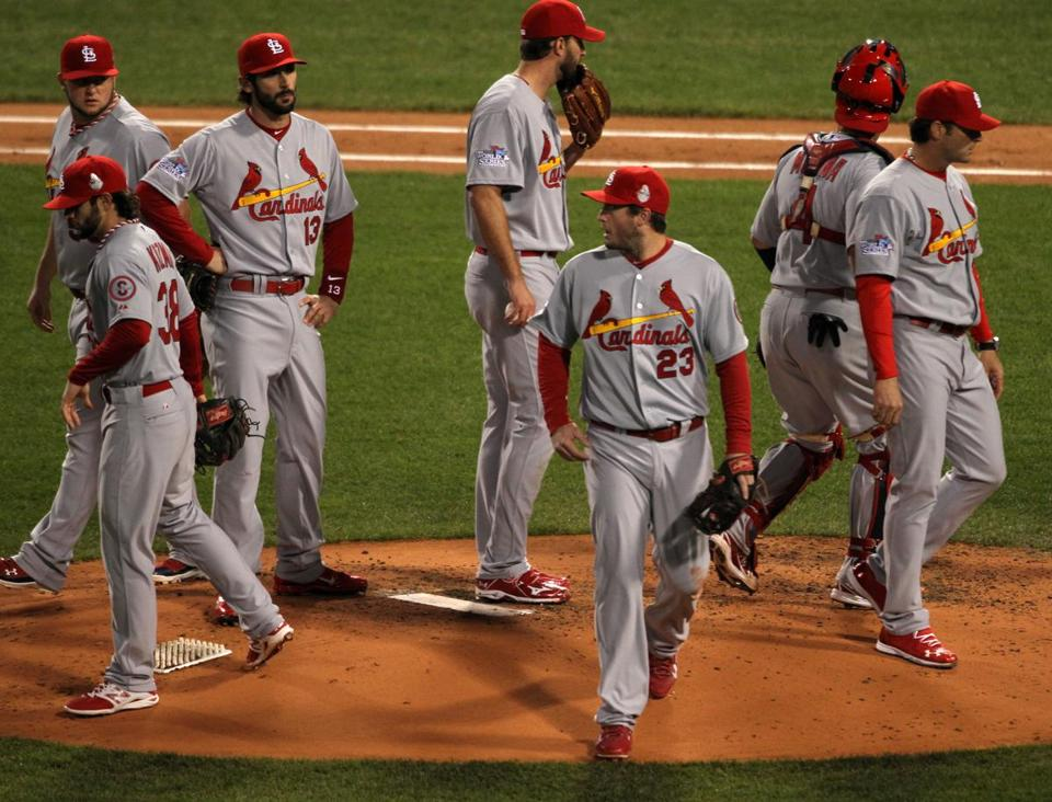 Cardinals pitcher Adam Wainwright (holding glove to face) was left behind as a second-inning mound meeting broke up.