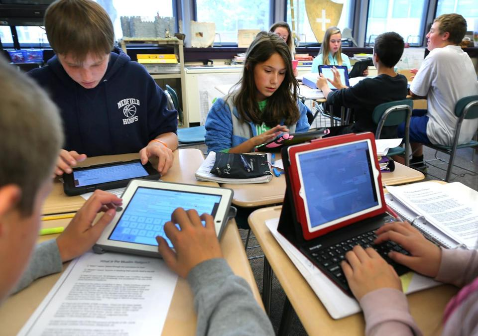 Blake Middle School eighth-graders tap into their iPads during a social science and history class led by Cynthia McClellan.