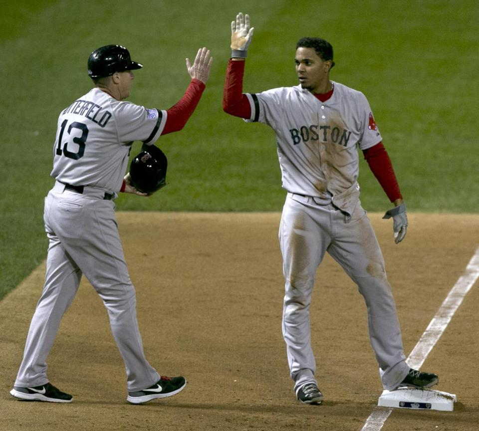 Red Sox Xander Bogaerts gets a high five from third base coach Brian Butterfield during game three of the World Series on Oct. 26.