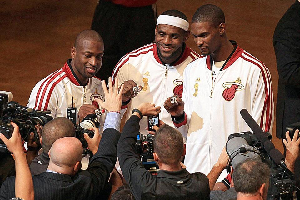Heat stars Dwyane Wade (from left), LeBron James and Chris Bosh show off their championship rings.