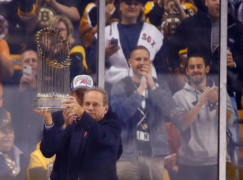 Larry Lucchino showed off the Red Sox' World Series trophy before the Bruins' game Thursday.