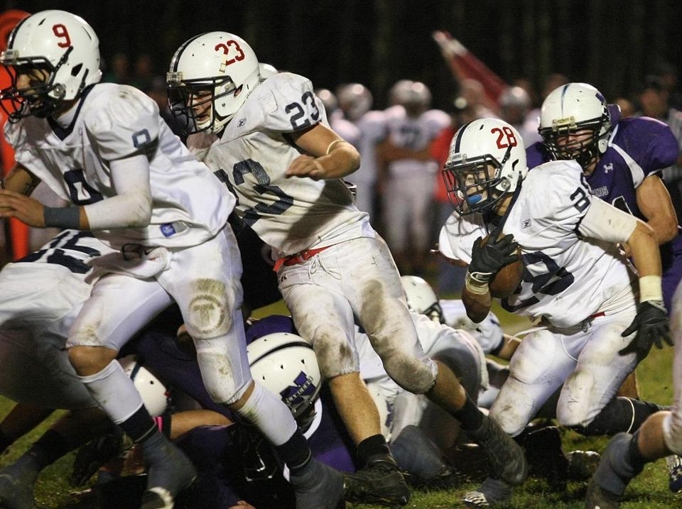 Apponequet's Cam Costa (left) and Westin Cohen (center) help clear the way for Matthew Michael's carry during the team's victory on Friday over Norton.