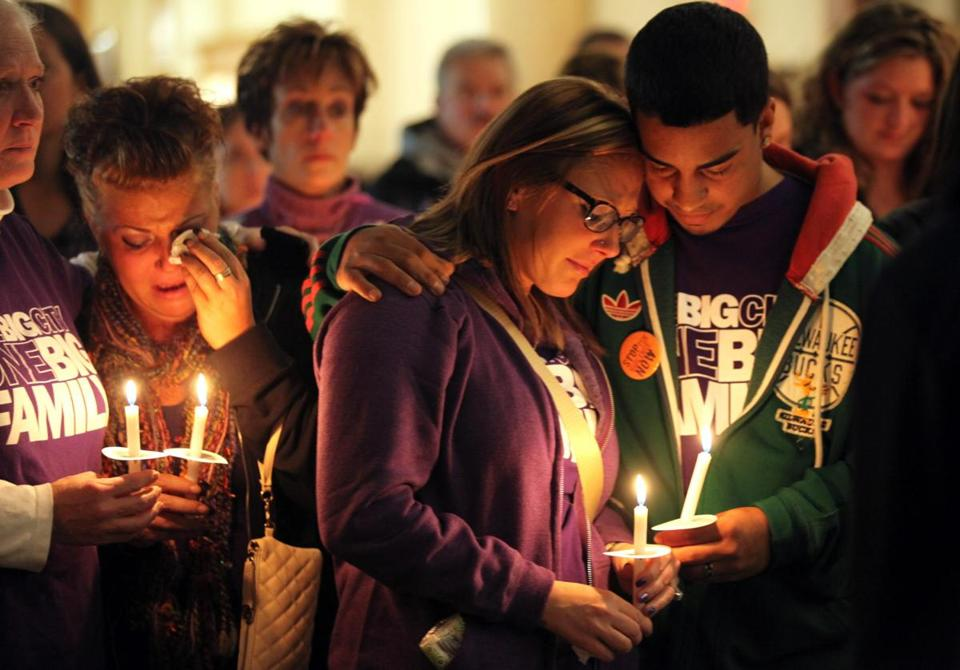 Mourners in Wisconsin hold a vigil in October marking the one-year anniversary of a shooting at a hair salon.