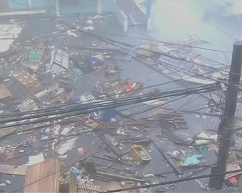 Debris floated on a flooded road as winds and rain battered buildings in Leyte province.