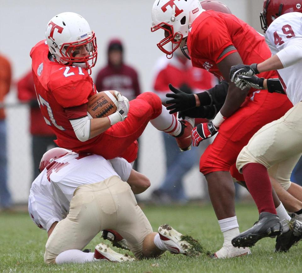 Dominic Rosado (27) of Tewksbury is upended on a kick return in the first quarter against Gloucester.