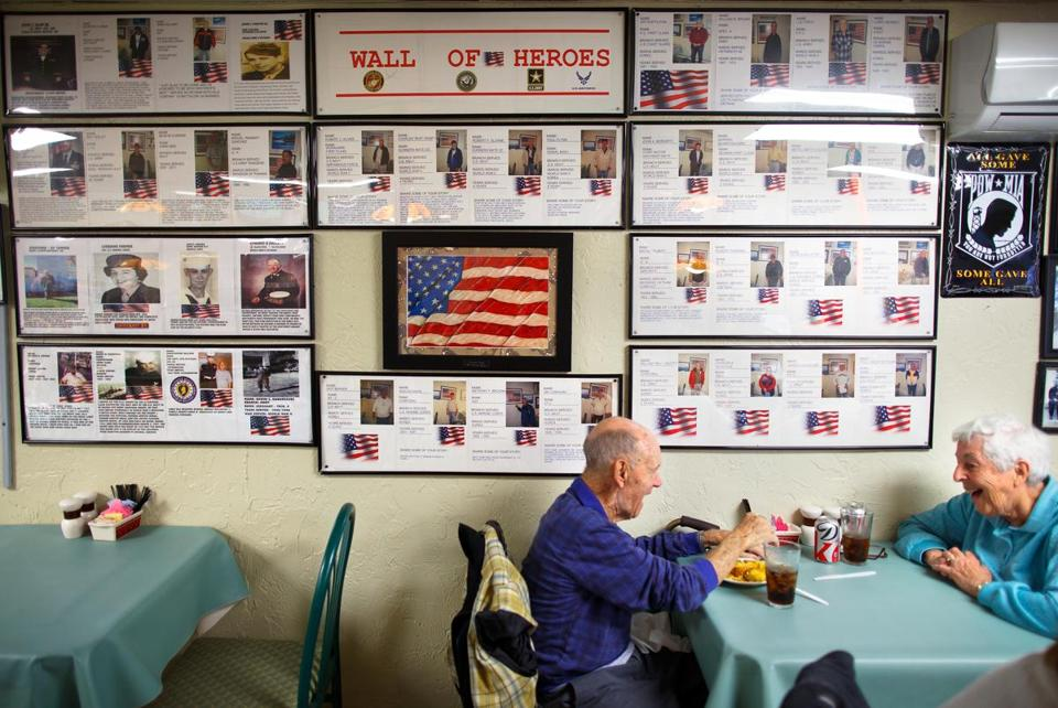 "Veterans John and Lorraine Farmer enjoyed their breakfast Sunday at a table in front of the ""Wall of Heroes"" at the Winthrop Center Cafe."