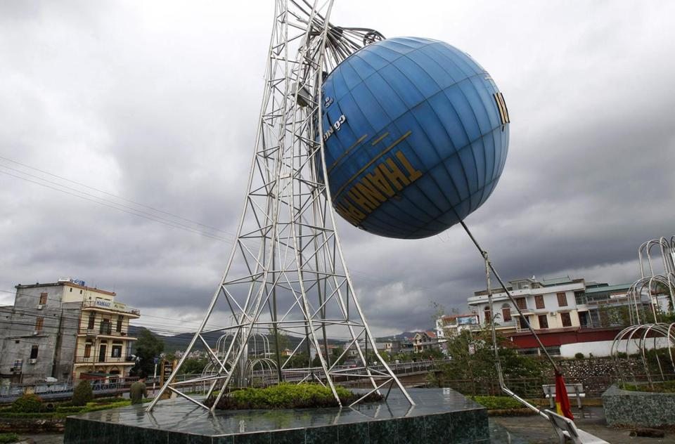 A man walked near a globe damaged by Tropical Storm Haiyan in Vietnam's northern Quang Ninh province.