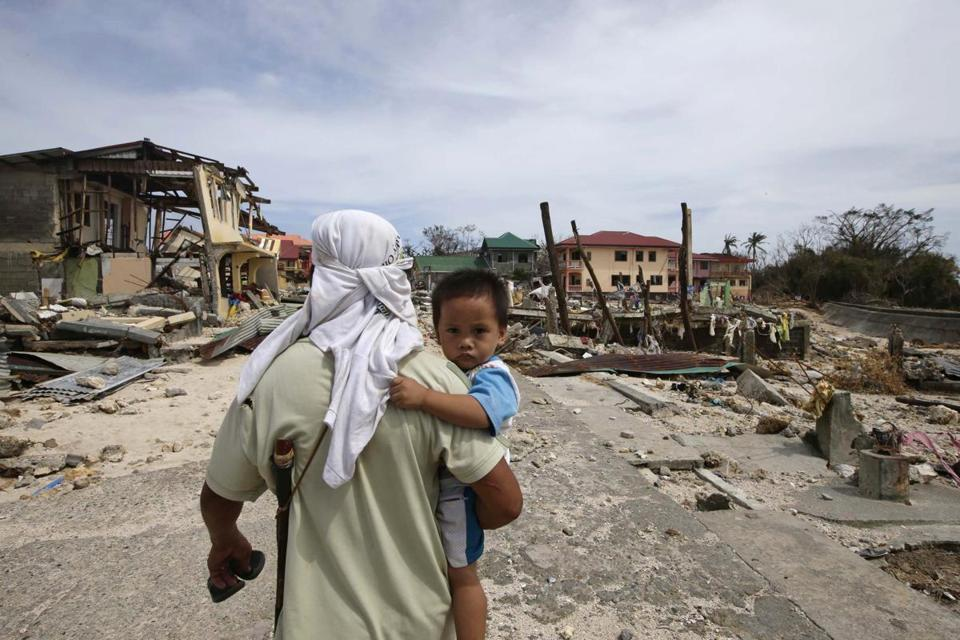 A man walked home with his son Monday in Hernani township, eastern Samar province, Philippines.