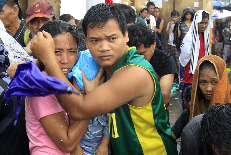 A husband and wife protected their baby from rain as they waited for an evacuation flight in Tacloban, Philippines.