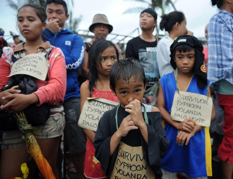 "Children wearing signs that say ""survivor"" waited for a C-130 military plane at Tacloban airport in the Philippines Tuesday."