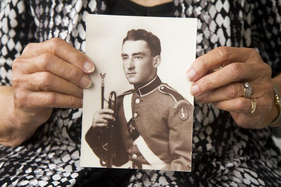 Marjorie Clark displayed a photo of her late husband, Army Sergeant Keith Clark, a virtuoso bugle player who missed a note while playing taps at President Kennedy's funeral.