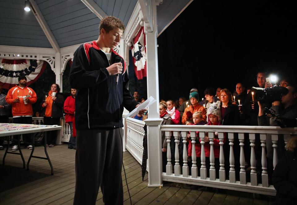 Lunenburg High School football player Isaac Phillips read a statement at a candlelight vigil Sunday that was organized to respond to racist graffiti painted on his house.